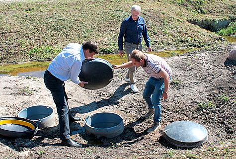 Kolm maasse kaevatud tünni on täidetud  kolme erineva filtreeriva ainega. P–filtrit tutvustab TTÜ keskkonnatehnika instituudi professor Arvo Iital (vasakul). Foto: Katrin Pärnpuu