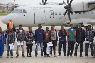 Italy Migrants Eritrean refugee pose for a group photo in front of an Italian Financial police aircraft which will take them to Sweden, at Rome's Ciampino airport, Friday, Oct. 9, 2015. The aircraft brings the first refugees to Sweden under the European Union's new resettlement program aimed at redistributing asylum-seekers from hard-hit receiving countries. (AP Photo/Andrew Medichini)